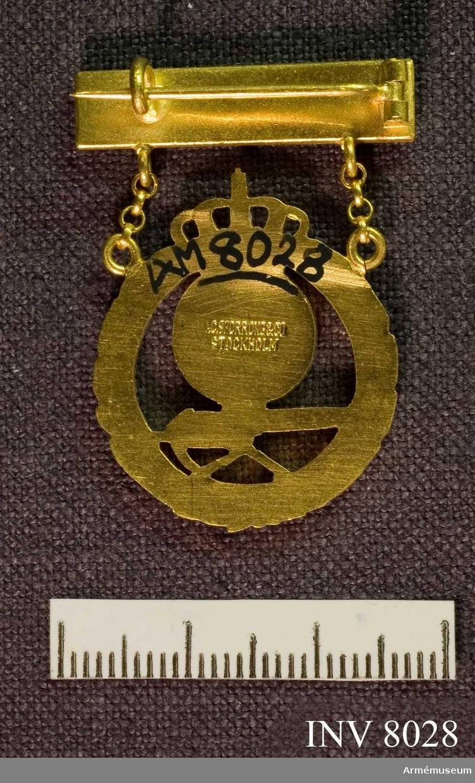 Kulsprutemärke i guld, årtalsmärke. Diameter 24 mm. Höjd 1 mm (tjockleken), längd 25 mm (plattan), bredd 5 mm (plattan). Märke i guld och blå emalj och gul emalj. Märket hänger i ett spänne på vars platta en emaljerad blå stjärna sitter.  I det runda märket sitter landstormsmärket i gul och blå emalj och under det en kulsprita i gul. Märket är statens utmärkelsetecken för det frivilliga  skytteväsendet.