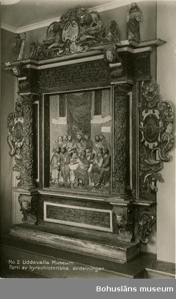 Altaruppsats från 1675, rikt skuren i trä med central skulpturscen, krön, sidostycken, pelare och kapitäl som krederats och målats med mager oljefärg samt förgyllts med oljeförgyllning. Förgyllningen uppvisar både bladguld, slagmetall och förmodligen silver, som mörknat påtagligt. Tillhörande skulpturer överst på ömse sidor om kröndekoren; UM394, UM395.  Centralmotivet skildrar nattvardens instiftande i en skulpturscen. Över scenen läses nattvardens instiftelseord på danska. Under skultpruscenen inskriften:  ANNO 1671 ER DENNE KIERKEBYGNING I JESU NAFN BEGYNT OCH UNDER PASTORIS JOANNIS COLSTRIPII FLID MEDH SIT INREDE ANNO 1675 FULBORDET MEDH MIDDEL FRA EGNE RINGE INTRADER, ANDRE GOT FOLCKIS TILHJELP OCH FORNEMMELIG H. KONGL. MAJIT:S WOR ALLERNADIGSTE KONUNG CAROLI XI TILGAWE AFF 150 RIXDALER.  Altartavlan komer från Norra Ryrs kyrka, riven 1873 och benämnd Norra Ryrs kyrka fram till år 1884, idag Lane-Ryrs kyrka.  UM000384, UM000385, UM000389a-i, UM000393a-i, UM000394, UM000395a-b, UM000401, UM000404a-b, UM000405a-g, UM005660:1-57 samt UM65.01.001 är samtliga inventarier från den gamla kyrkan.  Beskrivning av altaruppsatsens delar: a. Tavla med nattvardsframställning; h. 120, br. 104 cm b. Överdel; l. 224 cm c. Krön till överdel; br. 132, h. 58 cm d. Pelare; h. med platta över kapitälet 113 cm e. Pelare, som föregående h. 113 cm f. Sidostycke; i 2 delar I-II, h. med tappar 128, br. 67 cm g. Sidostycke; i 2 delar I-II, h. med tappar 131, br. 69,5 cm h. Underdel; l. 201 cm i. En lös del, tillhörande UM000393h  Altaruppsatsen ska enligt uppgift i artikel i Bohusläningen den 30 april 1963 vara skänkt till församlingen av Karl XI som ett led i försvenskningen av Bohuslän.  Ytterligare foto i Uddevalla museums kyrkliga utställning år 1920, se UMFA53292:0013, UMFA53710:0075.  Ur Nationalencyklopedin, NE.se: Altarprydnad Under 1500-talet utbildades i Italien en ny typ: en central målning eller skulptur, omgiven av en rik, klassiserande omramning. I den tyska renässansen utv