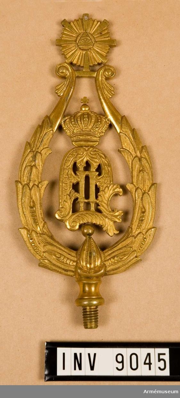 Spets m/1872 t fana, Hälsinge regemente.Spets O II t fana m/1894 f Hälsinge regemente I 14, II bat. Av förgylld metall med konungens monogram omgivet av en krans, spetsformad.  Samhörande nr är 53/156 + 9044-9045.