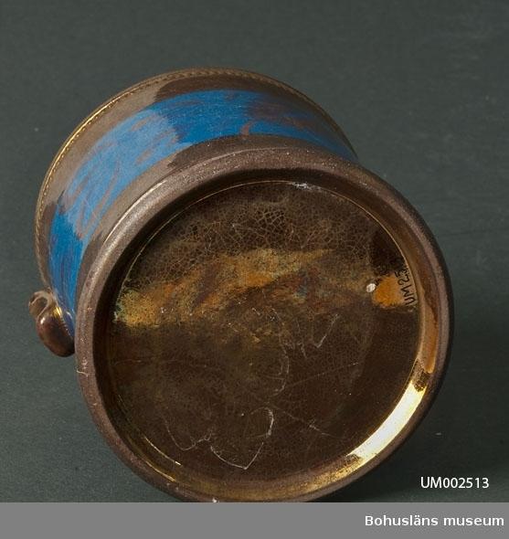 Cylindriskt kärl. Muggen är täckt med kopparlyster och har ett blått, brett fält runt livet. I det blå fältet är det en handmålad dekor i form av blad i kopparlyster. Dekoren ligger under glasyren. Vid mynningens utsida finns en pärlliiknande rad. På mynningens insida är det en rand med rosa lyster. Hänkel saknas.  Ur handskrivna katalogen 1957-1958: Mugg, porslin, handtag. def. Bottendiam.: 10,5. H: 10,3 Bronserad och blåfärgad. Handtag saknas. En spricka; eljest hel.  Lappkatalog: 62