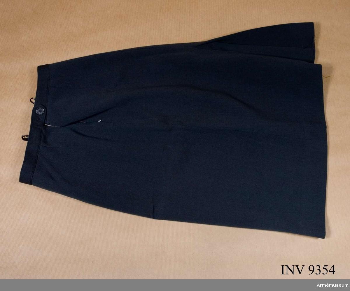Tillverkades åren 1960-1966 av stålgrå yllediagonal, 100 % ull. Kjolen är utförd med blixtlås i sidan, vänster sidsöm, förlängt midjeband med knapp och knapphål samt s k biljettficka i linningssömmen på höger framsida. Är försedd med motveck i bakvåden. Två hängare fastsydda i linningssömmen. De är märkta med tillverkarens firmanamn Te-Be-We / Thure B. Wiberg, Malmö. Övrig märkning: På fickpåsens yttersida stämpel: Tre kronor 1963. På linningens insida framtill vävd storleksetikett: 40. Gåva från FMV i Solna.