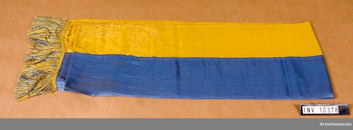Grupp B I. Fana för Norrlands trängkår m/1935. Samhörande spets, kravatt och fodral. Ljusblå fanduk och visar på mitten det krönta lilla riksvapnet  omgivet av vita strålar  och tungor. I det övre inre hörnet den vita renen i landskapet Västerbottens vapen. Stången vit och  spetsen med Gustaf V:s namnchiffer. Överlämnad jämlikt Go 3596/1951.