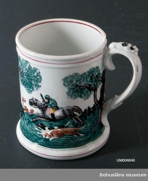 """Svagt uppåt avsmalnade kärl med hänkel. Vit med polykrom dekor i relief. Motivet visar en jaktscen - en jägare till häst som jagar en hjort. På hänkelns ovansida ligger en hund. Under botten står det intryckt: """"GUSTAVSBERG"""" samt en trea (3). Föremålet är krackelerat. Det är ett urslag i mynningskanten.  Ölost (eller ölsupa, ölsoppa) är en traditionell bohuslänsk dryck som bygger på svagdricka och mjölk som kokas och vispas. Recept se UM005098.  Ur handskrivna katalogen 1957-1958: Ölostmugg Mynningsdiam. 11,8-12,2 H. 15,5. Vitt porslin med jaktmotiv i färg. Obetydligt skadad i kanten.  Lappkatalog: 62"""