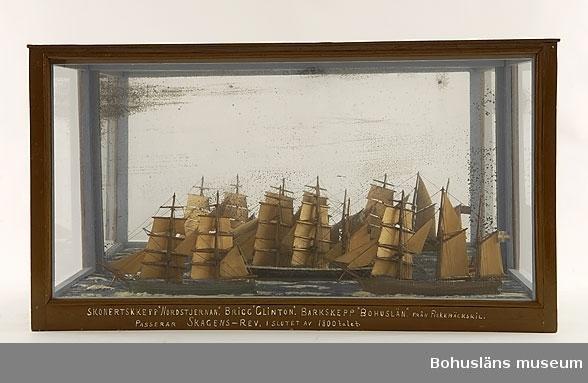 """Panorama med skonertskeppet Nordstjernan, briggen Clinton, barkskeppet Bohuslän och fyrskeppet Skagens rev.  Modellen tillverkad av kapten John Emil Olsson (1880 - 1950), Fiskebäckskil på Skaftö i Lysekils kommun på 1940-talet. Trä, metall, lintråd, glas, spegelglas, gips, målat med oljefärg.  Fartygsmodeller höjd 14 cm, längd 27 cm, bredd 3,5 cm.  Monterns mått 71 x 33 x 39 cm. Okänd skala. Vattenlinjemodeller av fyra fartyg, från vänster Clinton målad grön, Bohuslän målad svart, Norstjernan brun och Skagens rev är röd. Stående och löpande rigg, segel av snidat trä och unionsflaggan hissad på mesanmasten. Däckshus och lastluckor. Monterade på en utskuren rektangulär träplatta med modellerad och målad gipssjö, placerad i en monter mot en spegelbakgrund.  Framtill på modellens långsida står textat med vita tryckbokstäver:  SKONERTSKEPP """"NORDSTJERNAN"""". BRIGG """"CLINTON"""". BARKSKEPP """"BOHUSLÄN"""" FRÅN FISKEBÄCKSKIL. PASSERAR SKAGENS-REV I SLUTET AV 1800-talet.   I Sjöfartsbok för John Emil Olsson utfärdad vid Uddevalla Sjömanshus framgår att han var mönstrad som jungman på briggen Clinton för resa till Hudiksvall m fl orter 7 maj - 7 oktober 1896. Detta var första gången John Emils gick till sjöss. Han skulle snart fylla 16 år. Befälhavare var 24-årige G. J. Bengtsson.  16 mars - 18 oktober 1899 mönstrade John Emil åter på Clinton som lättmatros för resa Göteborg - England och vidare under befälhavare P. Simonsson.  När briggen Clinton köptes av Fiskebäckskilsredare för fraktfart i svenska vatten hade den ett mörkt förflutet som amerikanskt slavskepp för transport av slavar mellan Afrika och Amerika. I trävirket fanns fortfarande de ringar kvar som slavarna varit fastkedjade vid under överfarten. Fyrskeppet Skagens rev var ett av de danska stationära fyrskepp som varnade sjöfarare som passerade Skagens nordligaste udde, Grenen. Skagens Odde är gräns mellan Skagerrak och Kattegatt, en av Europas viktigaste handelsleder och danska Jyllands nordligaste del. Skagens rev är den g"""