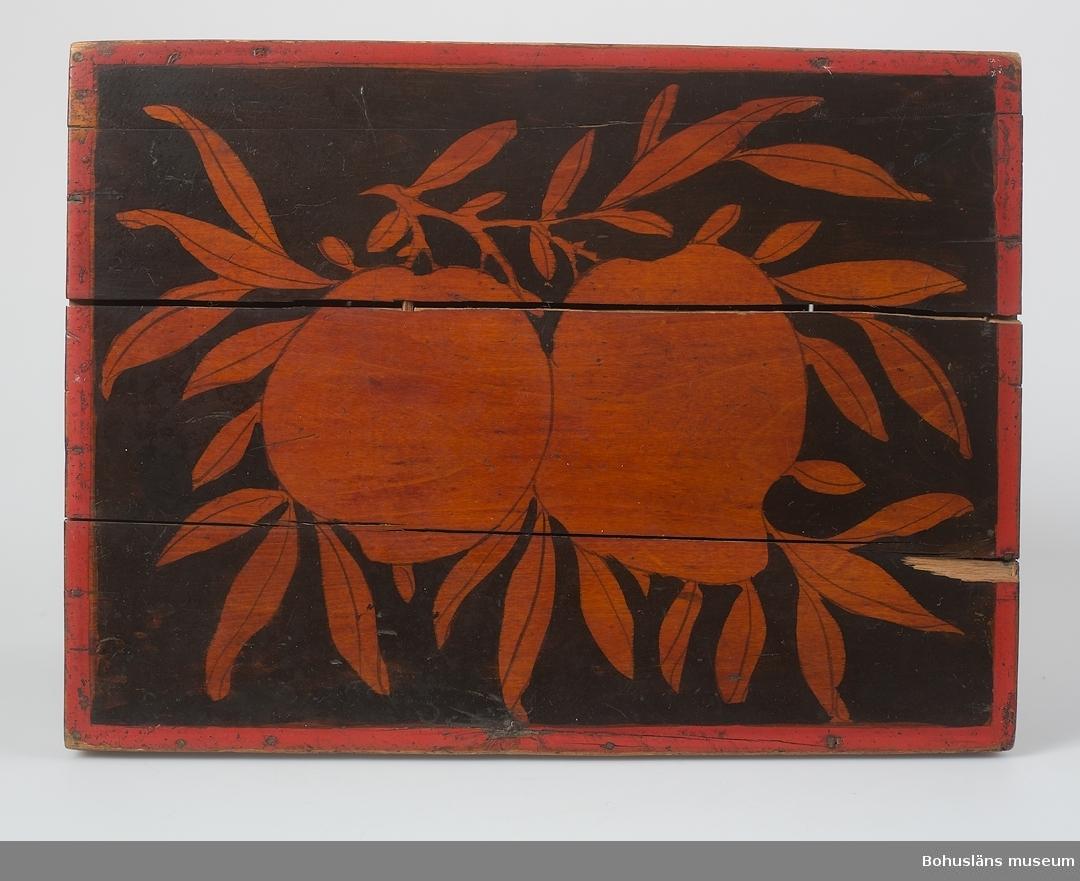 Rektangulär form med platt lock. Handtag bestående av böjd metalltråd på vardera kortsidorna. Svart/brun målning på orange (träets färg efter bets?) botten med rödmålade kanter. Locket har fruktmotiv. Kortsidorna har blomdekor. Framsidan har en figurscen och baksidan ett landskap. Inuti finns spår av fackindelning. Säckvävsrester i botten samt fragment av papper med kinesiska? tecken i svart och rött i locket. Lås samt handtag på höger sida saknas. Flertalet horisontella sprickor. Är enligt äldre katalogkort från Ostasien.  Ur handskrivna katalogen 1957-1958: Skrin från Ostasien L.: 32 cm. Br: 24 cm. H.: 26 cm. Målat i svart o rött m. figurer i svart o rött, blommor, frukter m.m. Lås saknas. Skrinet ngt trasigt i fogarna. G. av fru Rosa Jacobowsky.