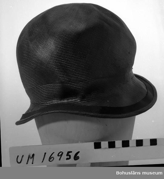 Tätslutande kulle, smalt utstående brätte, 1920-talsartad modell.  Import från England för försäljning hos Strand Mode. Band kring kullen saknas. Se UM16935.