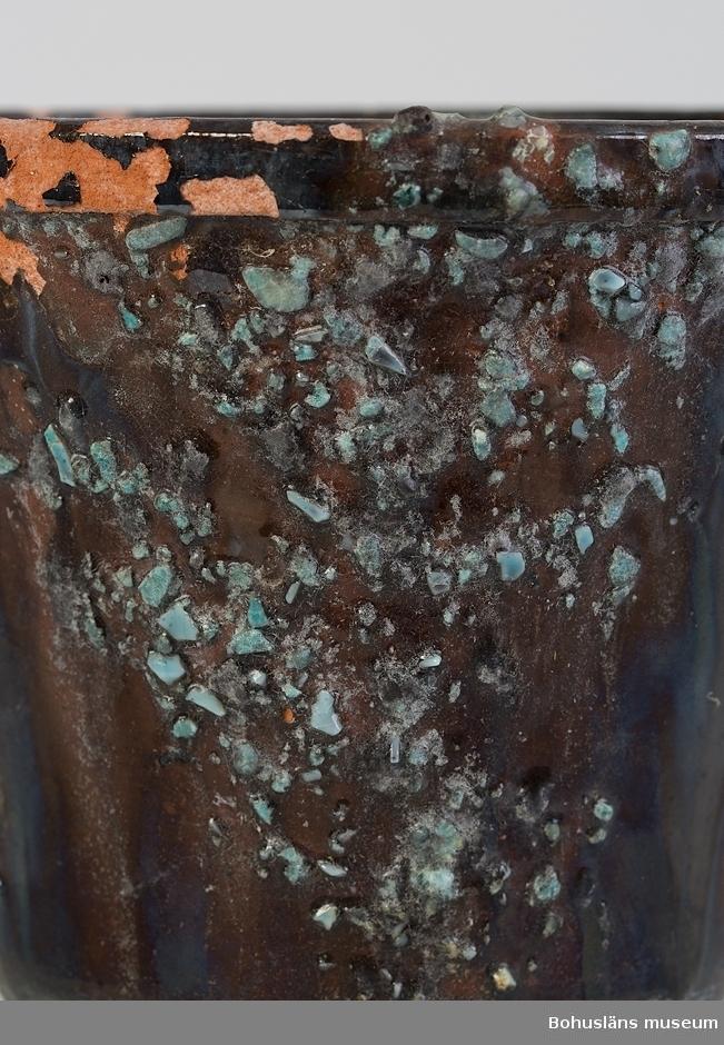 """Blomkruka, svartglaserad med dekor i blåturkos. Diameter botten 10,6 cm. Nästan rakt koniskt öppen form. Drejat rödgods med bearbetad kantdel, hål för vattenavrinning i botten, brunsvart glasyr, dekor av svagt blågrön chamotte i fyra oprecisa vertikala områden på utsidan. Chamotten består förmodligen av krossat glas/mosaik. Oglaserad inuti. Skador pga användning. Rester av jord inuti. Användningstid uppskattad.  Krukan kan härstamma från krukmakarsläkten Hjoberg som haft krukmakeri i Västra Bodane, Frändefors socken under stora delar av 1800- och 1900-talen.  Litteratur: Hembygden, Dalsland 1973, """"Pottkakelugnen"""", om krukmakarsläkten Hjobergs kakelugnstillverkning, av Christer Järlgren, s. 25-58;  """"Krukmakare och kakelugnsmakare"""", Tom Möller, Raster förlag (1999), s. 22-27.  Bilagepärm UM018181 Informationsblad """"Välkommen till Hjoberg krukmakare på Dal"""" (2000-talets början) samt """"Hjobergs krukmakeri"""" (1997)."""