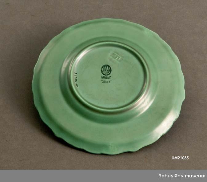 """Gröna assietter, stämplade i botten med fabriksmärke och """"Made in Sweden"""" samt """"2853"""". Fabriksmärket är inpressat i godset."""