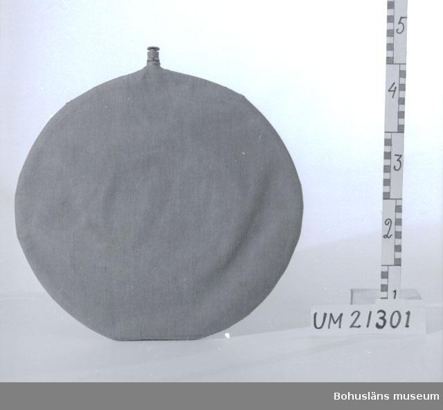 594 Landskap BOHUSLÄN  Platt gummiflaska med metallpropp. Skyddshölje i grått bomullstyg.  UMFF 8:11