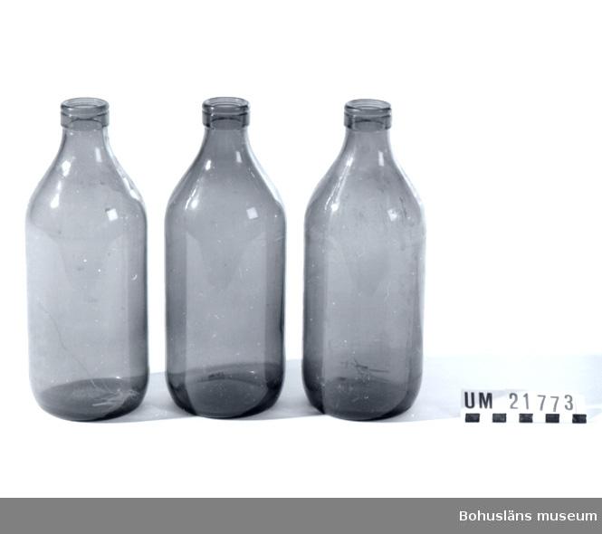 """Förpackning för mjölk. Flaskorna märkta i botten med följande text: """"1 Lit (L) ll 64"""". De två andra flaskorna är märkta med följande text: """"1 Lit (L) 9.64""""."""