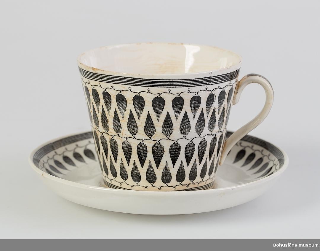 Koppen krackelerad, tefatet felfritt. Föremålen dekorerade med stiliserad bladmönster i svart koppartryck på vit fond.  Formgivaren Arthur Percy född 1886 i Vickelby på Öland.