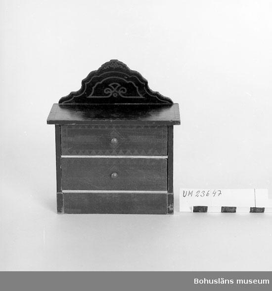 594 Landskap BOHUSLÄN  Byrå med två lådor och profilsågat ryggstycke. Betsad för att likna mahogny. Geometrisk dekor i guldfärg på front, skiva och ryggstycke.  Neg. nr UM 148:6