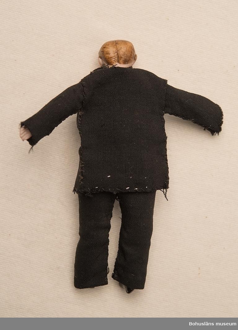 Mansdocka med tygkropp och nederarmar, nederben och huvud av biskviporslin. Huvudet bemålat. Vänsterfotens yttre hälft avbruten. Försedd med troligen hemmasydda kläder; vit skjorta, svarta byxor, svart väst och kavaj. Dockans kropp är hemtillverkad.