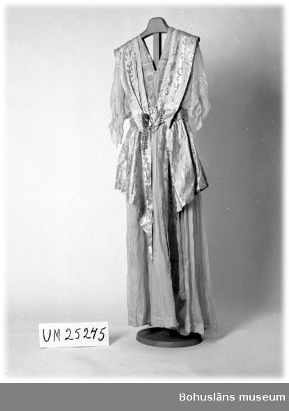 """Kjol bestående av ljust violett (syrenlila) siden med överkjol av vitt, mycket tunt glest siden längs vars fåll broderats en rad glaspärlor. Bristningar i båda kjollagren. Liv med underdel av metalltrådsbroderad tyll. Över detta ett liv av tunt, glest vävt tyg av samma slag som i kjolen. V-ringning bak och fram. Korta ärmar med sydda stråveck och flikformad nederkant med glaspärlbroderi. Över livet och två tredjedelar av kjolen liknande arrangemang av ljust violett, mönstervävt siden närmast akantusliknande mönster, ihophållen i midjan av smycke bestående av två rundlar och däremellan flera rader av ljust lila pärlor. Några pärlrader skadade. Nederkanten avslutas med två långa flikar, broderade med såväl små, ofärgade glaspärlor samt något större ljuslila. Mellan varje större pärla fyra små. Klänningen använd på en av Uddevalla Curlingklubbs årliga baler, vilka brukade hållas på Grand Hotells festvåning, Uddevalla. Medlemmar av familjen Thorburn var med och grundade curlingklubben. Gåva av brukarens dotter. Brukaren ANNA Sofia Thorburn, född Lindskog den 20 juli 1866 i Strömstad, dotter till tullförvaltaren P.N. Lindskog och hans hustru, död 27 december 1939 i Uddevalla. Anna Thorburn gifte sig 1887 med den danske vicekonsuln och direktören för Badö Oljelager ALBAN Edvard Thorburn, född 1862 i Uddevalla, son till grosshandlaren Robert Thorburn och Alma född Jacobi, och död den 29 november 1933. Klänningen utställd på Bohusläns museums modeutställning """"Tidsspeglingar"""", vilken visade 1900-tals mode, hösten 1990/nyåret 1991. För ytterligare personuppgifter om Anna och Alban Thorburn se bilaga samt dödsruna i Bohusläningen torsdagen den 30 november 1933 och Bohusläningen den 29 december 1939."""