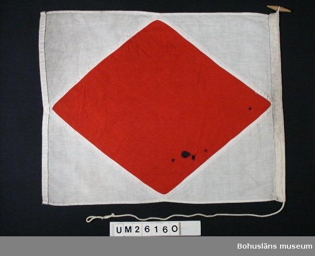 """Föremålet visas i basutställningen Kustland, Bohusläns museum, Uddevalla.  Rött rombiskt fält mot vit botten.  Betyder: """"Jag är havererad. Sätt er i förbindelse med mig"""".  Bristningar, hål. En av de tre signalflaggorna med samma betydelse har större mått: B 56,0 H 44,5 cm.  Använd för fartygssignalering på Ångfartygs AB Bohuslänska Kustens båtar. Användning se UM026139  Personuppgifter se UM026024"""