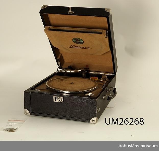410 Mått/Vikt  TJ 17 CM  Svart bärbar grammofonlåda. Invändigt med skivtallrik,  pickup på rörlig arm samt vev för uppdragning av spelverket. Avsedd för 78-varvsskivor, s. k. stenkakor. I locket förvaringsbox för skivor. Tre små plåtaskar av olika märke för grammofonstift som fick bytas med  jämna mellanrum. Personuppgifter om ägaren se UM26259.
