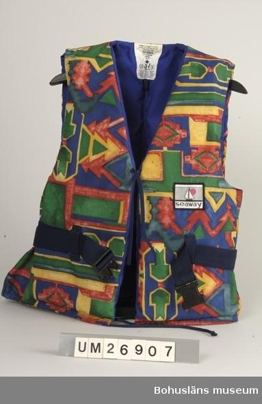 """V-ringad segelväst med utsida av mönstrat polyamidtyg i blått, gröna nyanser, gult och gultonat rött. Mönstret är rektanglar, linjer och pilar som går in i varandra till ett heltäckande ytmönster. Foder av klarblått polyamidtyg. Fyllning av två rektangulära block av """"flytmaterial"""" insydda i ryggstycket mellan tyg och foder och ett block, format efter västens form, i vardera framstycket. Sidostycken i enkelt tyg utan fyllning. Ett tygmärke upptill på vänster sida i svart, mycket ljust beige och blårött (ceriserosa): Föreställer en segelbåt och en sol och under dem texten """"seaway"""". I midjehöjd hällor av blått polyamid?band, en bak och en på vardera framstycket. Genom hällorna är ett skärp av blått polyamid?band draget. Det knäpps ihop fram med ett svart plastspänne. Knyttampar finns upptill mitt fram och nertill finns snodd att dra ihop vidden med. Fållen bildar en kanal för snodden. Invändig tygetikett i nacken. På den står bl.a. """"70-90 KG"""" och där finns en stiliserad bild på en människa med huvud och armar ovanför vattenytan. Stor etikett invändigt i vänster sida. Under rubriken: """"Flytplagg 50 N"""" finns där användningsanvisningar på svenska. Samma text finnns på ytterligare nio språk. På den stora etiketten finns även skrivet: """"Model: 96015503504066"""" med svagt synliga siffror: """"Denna väst är godkänd enl: CE94EN393"""". Vidare finns tillverkarens namn och adress samt storleksanvisning. Små mögelfläckar fram.  Inköpt på Sjösport, Norra Allégatan i Göteborg 1995. Flytvästen  är en del av säkerhetsutrustningen.  Insamlad i samband med SAMDOK-dokumentation av båtturism.  För fler uppgifter om brukaren se UM26869."""