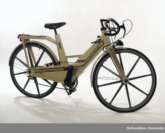 """Sportmodellen av Iteracykeln med utanpåliggande växel och bockstyre. Kakifärgad. Allt på cykeln i original utom greppbanden på styret. Bakskärm trasig, fläckig sadel. Se utförlig artikel om Itercykelns uppkomst och misslyckade försäljning i  Varbergs museums årsbok 1994. Till cykeln hör en reparationssats med en """"Montera-själv-anvisning"""" UM027265:2 samt  en handbok - se Bilagepärmen UM27265.  Cykeln har först använts som uthyrningscykel för turister av ett företag i uddevallaområdet, men blev inte så populär där eftersom den uppfattade som instabil då den hade en tendens att """"vobbla"""" när den var tungt lastad. Givaren köpte denna cykel av uthyrningsfirman för 500 kronor och använde den under några år för att köra kortare sträckor. Därefter har den stått undanställd. Givaren köpte cykeln på grund av att den var en teknisk innovation och lite spännande. Enligt givaren såldes begagnade Itera-cyklar till Söderhavet där de uppskattades för att de ej rostade i den fuktiga miljön.  Insamlingsgruppen tackade först nej till erbjudandet och vidareberfodrade det till Röhsska museet, Göteborg, eftersom cykelns formgivningshistoria är intressantare än dess historia i bohuslänska sammanhang. Där tackade man emellertid nej eftersom cykeln inte var i nyskick. Eftersom den har en historia i Bohuslän - Sveriges plastlän -  och är ett exempel på en mycket uppmärksammad produkt i detta material, har den ändå en plats i museets samlingar."""