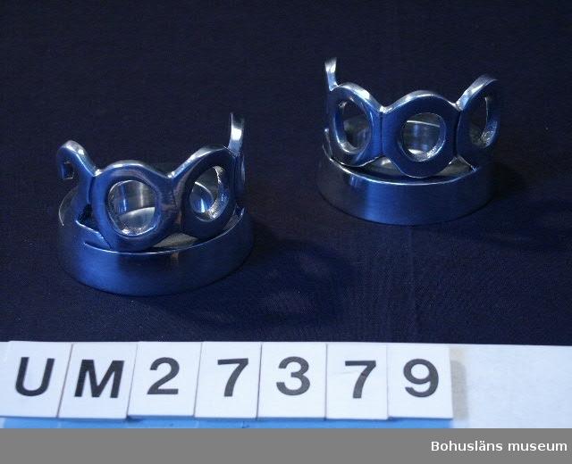 Ett par runda värmeljushållare med hålighet för ett värmeljus och på kanten dekorerade med siffrorna 2000. Sandgjutna, på utsidan silverfärgade och polerade.   Inköpta i Uddevalla för 45 kronor styck.  För information om Millennieinsamlingen, se UM27360.