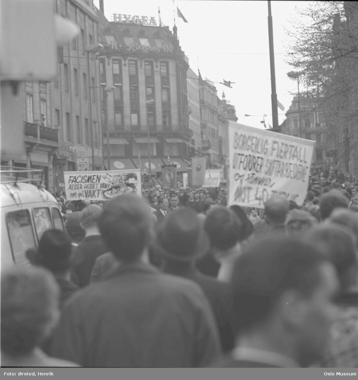 1. mai-feiring, 1. mai-tog, mennesker, demonstrasjon, paroler, faner, forretningsgårder