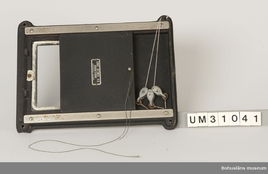Brandlucka  eller filmgardin av svartmålat gjutjärn och glas. Om filmprojektorn började brinna föll luckorna ner och hindrade eld och rök att sprida sig in i biografsalongen. Luckan regleras och hålls på plats med hjälp av en bomullsnitrattråd som löper i tre små block. Denna är mycket lättantändlig. På luckan sitter en metallskylt med texten:  ERNST DITTMER A.B. BIOGRARTEKNIK STOCKHOLH (Sweden) Vid användning av kolstavar och bågöampor utvecklas mycket hög värme.  Har använt tillsammans filmgardin UM31042 och  projektor UM31031.  Se foton på gardinerna på sin ursprungliga plats tillsammans med gardinerna, UMFA  Projektorn är tillverkad av AEG på 1920-talet och har använts i Folkets Hus i Sjöbol vid Lysekil.  Till projektorn hör en lång rad delar och olika tillbehör, UM31031 - UM31062.  För ytterligare upplysningar om filmprojektorn, dess olika delar och användning, se UM31031.