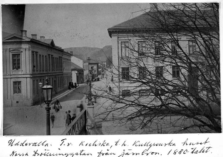 """Text på kortet: """"Uddevalla. T.v. Kochska, t.h. Kullgrenska huset, Norra Drottninggatan från järnbron. 1880-talet""""."""
