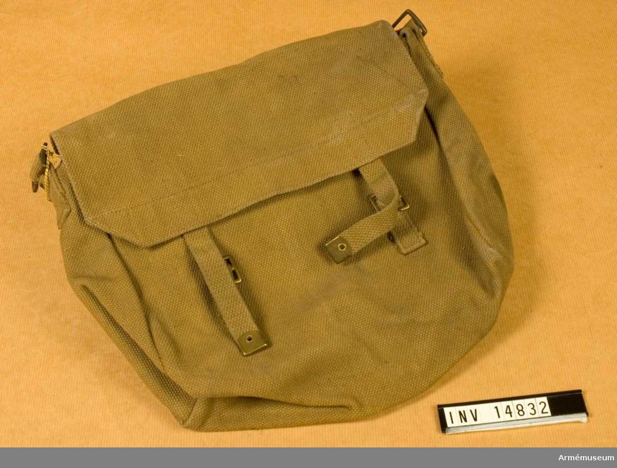 """Grupp C II.  Brödväska av khakifärgat tjockt bomullstyg (eng. wibbing). Den stänges med ett lock som har två remmar av samma tyg med spännen och beslag av mässing. På väskans båda sidor finns två fastsydda spännen för att koppla väskan till axelgehänget.   Lockets baksida har en stämpel med påskriften: """"M. E. Co. 1913""""."""