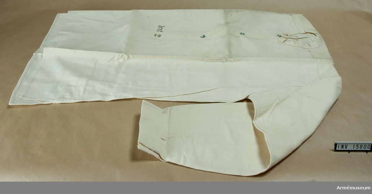 """Grupp C. Skjorta av vitt bomullstyg utan krage. På bröstets öppning finns tre knappar - små av järn. Samma knappar - en på varje - finns på ärmuppslagets sprund. På framsidan finns stämpel: """"Int.2"""" - intendentur 2."""