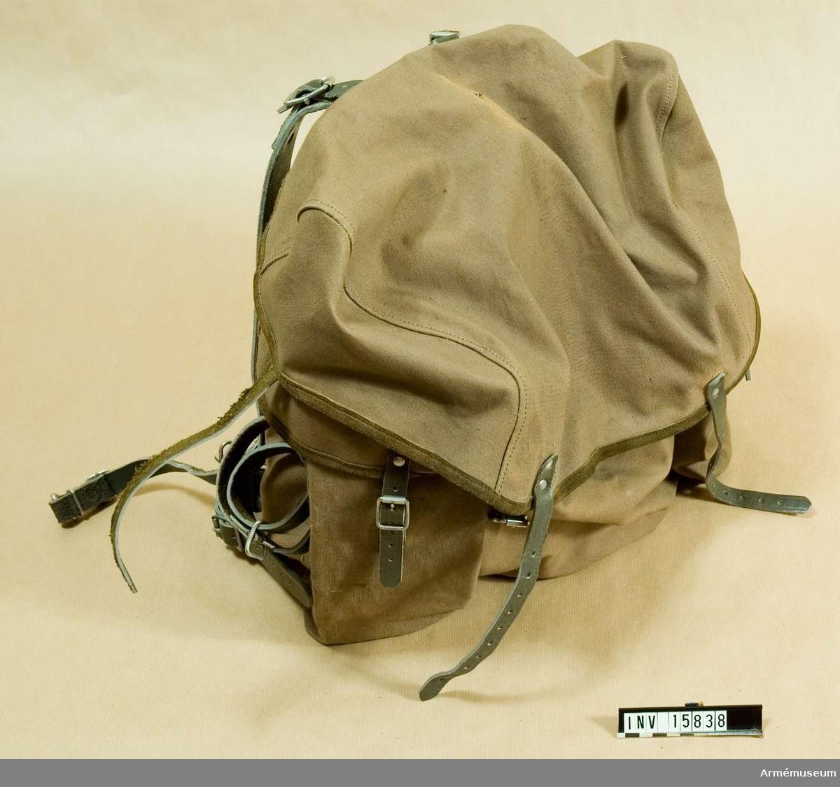 Grupp C 1. Ryggsäck av norsk modell med botten av järn (triangelform) med bälte av järn (halvrund). Säcken är av impregnerat brunt tyg med två sidofickor. Säcken bindes fast med grönt snöre och stänges med två remmar med spännen. På sidan av säcken finns remmar för att packa stövlar eller pjäxor. På ryggsäckens baksida finns remmar för att järnstängerna inte ligga på ryggen och längs midjan finns ett bälte av tjockt bomull. Säcken har två axelremmar för att bära säcken.