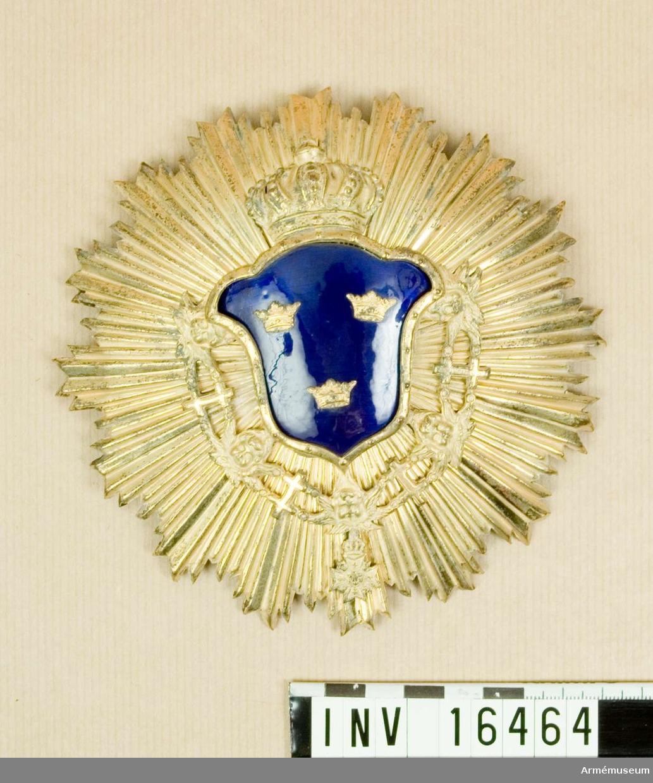 Av mässing med riksvapnet av blå emalj krönt med kunglig krona och med Serafimerordens kedja. Alltsammans placerad på en strålkrans.