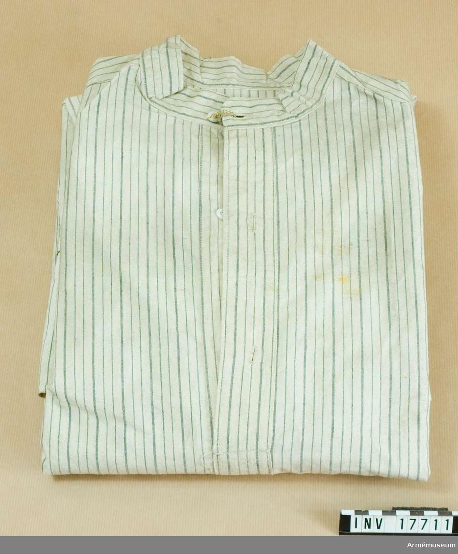 """Grupp C:1 Ur uniform m/typ 1923 (blå) för manskap för 24. infanteriregementet förlagt i Paris, Frankrike, bestående av vapenrock, byxor, kappa, benlindor, halsduk, hjälm, livrem med tre patronväskor, hängslen, bajonetthylsa, bärremmar, ränsel av kanfas, kokkärl, tältduksdelar, tältstångsdelar, tältpinne, filt, dricksflaska med yllefoder, mattornister, kängor, skjorta, dödsbricka, gevär med bajonett plus figur. Skjorta av bomullstyg, vit med grå ränder med fast upprättstående krage och långa ärmar. På bröstets öppning två  knappar, på kragen en. Alla knappar är små och vita. Samma knappar på ärmuppslagens sprund, en på varje. På skjortans baksida finns en stämpel: """"Rambouillet l-43, 1948"""". Litteratur: Collection complete des tracés de coupe des Effets d'Habittement a l'usage de tous les corps de l'armée, 1845-47 pour la Commission des modeles, sid 3: Skjorta, ritning med mått.Enligt kapten W. Granberg (med blyerts: 1957)."""