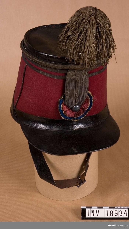 Grupp C I. Käppi m/1860 för officer vid Norska kavalleribrigaden. Av rött (karmosin) kläde. Rak skärm av svart läder. Käppin är täckt med svart läder ovanpå. Längs nedre kanten finns svarta läderband, 2 cm breda. Vid käppins övre kant finns två silvergaloner i mitten. Mellan knappen och käppins övre del finns två guldgaloner. På käppins framsida finns pomponhållare i form av en ficka med pompon av silversnören och hängande plym av silke i silverfärg. Foder av läderbitar, fästade med snören (som saknas). På käppins botten finns foder av bomullstyg i beige färg. Hakremmar av svart läder. LITT  Handbuch der Uniformkunde, Knötel-Sieg, Hamburg 1937. Sida 259. II Kavallerie. År 1860 infördes för norska kavalle- riet röd käppi med pompon av vitt garnityr. Bild. Abb. 102. Kavalleristen G. med likadan käppi. Svenska och Norska Armén. Bild, Kavallerist vid Kungl. Norska Cavalleribrigaden. Officerskäppi i samma stil men med andra kännetecken. Norska Armeens Uniformer, Album med bilder. Kavalleriofficer vid den kungliga Norske Cavalleribrigade.Enl kapten W Granberg 1953.