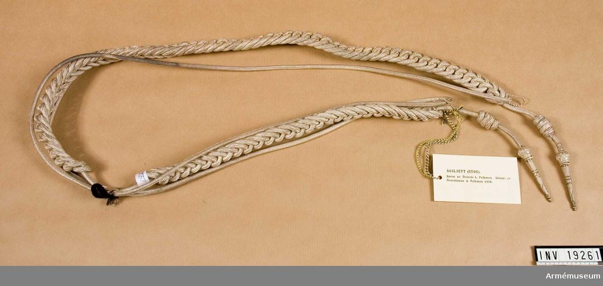 Stor ägiljett flätad i silver med ryhmnålar.
