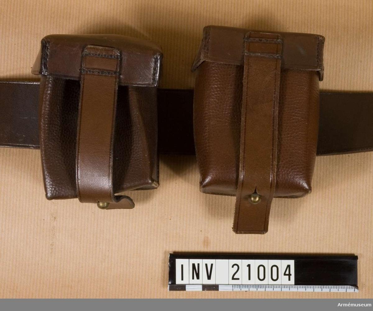 """Grupp C II. Av brunt läder. För tre patronknippen om fem st. i var. Patroner för gevär m/1898. Väskan stängs med remmar och knappar. På baksidan finns en rem för att fästa väskan vid livrem.  På var sida om livremsspännet placeras två väskor av vilka den ena har en ring för att kopplas till tornister med axelrem. På väskans baksida finns en stämpel, """"Loh Söhne, Act. Ges. Berlin"""". Väskan har en pappersetikett med text """"Tyskland"""", """"Lifrem med patronväska, bajonettbaljhylsa fastställt för den Ostasiatiska expeditionskåren. Vigt: 625 g. Bekommen 1901. År 1900 grundades Ostasiatiska expeditionskåren""""."""