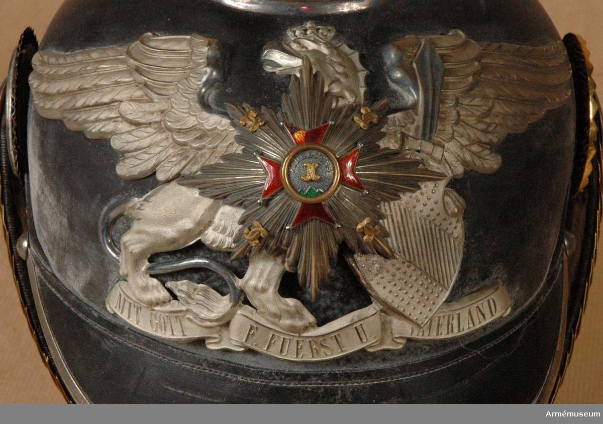 Grupp C I. Ur uniform för officer vid Badisches Leibgrenadierregiment. Består av kappor, kolletter, syrtut, vapenrock, ridbyxa, långbyxor, hjälm, mössa, skärp, sabel m tillbehör. Hjälm av svart lackerat läder med fram och bakskärm, avrundade. Framskärmen har beslag av vit metall. På hjälmens baksida finns en skena, som går från spetsen till nacken. Alla hjälmens metalldelar består av nysilver utom hakremmen som är av fjäll, s.k. tomlach. Foder av vitt skinn och siden med krona. Hakremmar av läder med ciselerade fjäll med rosetter av nysilver samt ett spänne. Kokarder: på hjälmens H sida under hakremsrosetten en svart- vit-röd =tyska nationalfärger. På V sida en gul-röd  =Badenska färger. Rikskokarden med ring av nysilver =officers tecken. Vapenplåt på framsidan med heraldiskt, badenskt vapen med stjärna. Enl W Granberg.