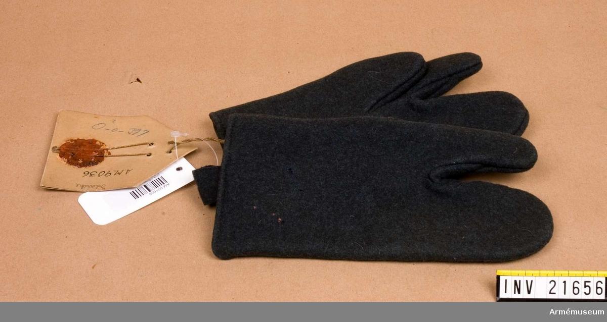 """Grupp C I. Ty. Fäustlinge. Av gråblått ylle mantelskläde med två fingrar - för tumme och pekfingrar. På vänster vante finns en mässingsknapp och på höger en fastsydd klädesbit med knapphål; allt för att sammanknäppa båda vantarna och hänga dem på livrem, när det ej användes. På vänster vante finns en stämpel (brun färg) """"898"""" =1898, """"H.G.S."""", """"2"""" =storlek. På höger dito stämplar - oläsliga. Pappersetikett med text """"Infanterie"""". """"Fäustlinge, zur neu eingeführten Adjustirung gehörig Gewicht von 9 bis 10 Lotz."""" LITT  Adjustirungs und Ausrüstungs Vorschrift für das K.K. Heer. l theil. Wien 1871. Sida 50. Fullständig beskrivning och två bilder på vantar (""""Fäustlinne""""), som äro lika dessa."""