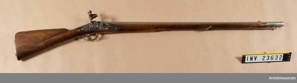 """Grupp E II.  Frånsett låset och den korta pipan liknar vapnet det vanliga infanterigeväret m/1747 (AM 1932:4121). Varken geväret eller bajonetten har några stämplar.   Det rätt höga, båtformiga mässingskornet sitter 10,3 cm bakom mynningen. På svansskruvsstjärten finnes ett gropsikte. Den främre bajonettklacken sitter 4,2 cm och den bakre 8,3 cm bakom mynningen.   Låset har platt, med bräckta kanter försett bleck. Eldståls- fjäderskruven och pannskruven gå inifrån. Eldstålet är upptill tvärt avskuret, men i motsats till infanterigeväret m/1747 har fängpannan arm.   Stocken är av björk och mörkbrun, men ursprungligen sannolikt svart. Kolven är falsad och detsamma är också framstocken längs laddstocksrännan. På kolvens vänstra sida inslaget numret 25. Beslagen är av mässing. De likna de å infanterigeväret m/1747, men bakplåtens flik är fäst med två skruvar. I den egentliga bakplåten sitta två stora, halvklotformiga huvud försedda skruvar. På kolvhalsen tom tumplåt, som närmast liknar en krönt sköld.  Laddstocken är av järn.   Bajonetten är en vanlig m/1747 och sitter till vänster.   Kratsen har två spiralklor och två fjädrande sidostycken. Den har upptill gängat hål för laddstocksänden.  I Modellsalens reversal kallas vapnet """"Infanterigevär, svenskt, med flintlås, 1747 Års för Jämtlands och Cajana bataljon"""". I 1813 års inventarium över Beväringsförrådets modellkammare finnes en """"Mousquette, 1747 års, korrt med Bajonette"""". Men i 1804 års inventarium över Generalfälttygmästareämbetets modellkammare upptages såväl en """"1747 års Modell, men pipan 8 tum kortare med bajonett och bajonettbalja"""" som en """"För Cajana Compagnie med ändrat lås av 1747 års modell, pipan 8 3/4 tum kortare är 1747 års, med bajonett"""". I 1780 års inventarium över Generalfälttygmästarekontoret återfinnes dels en """"Modell till Infanterie Mousquette, för Jämtlands regemente, approberad 1747, med Bajonette"""" och dels en """"D:o för Cajana Compagnie 1747, utan bajonette"""". Ganska sannolikt är att den bajonett, som"""