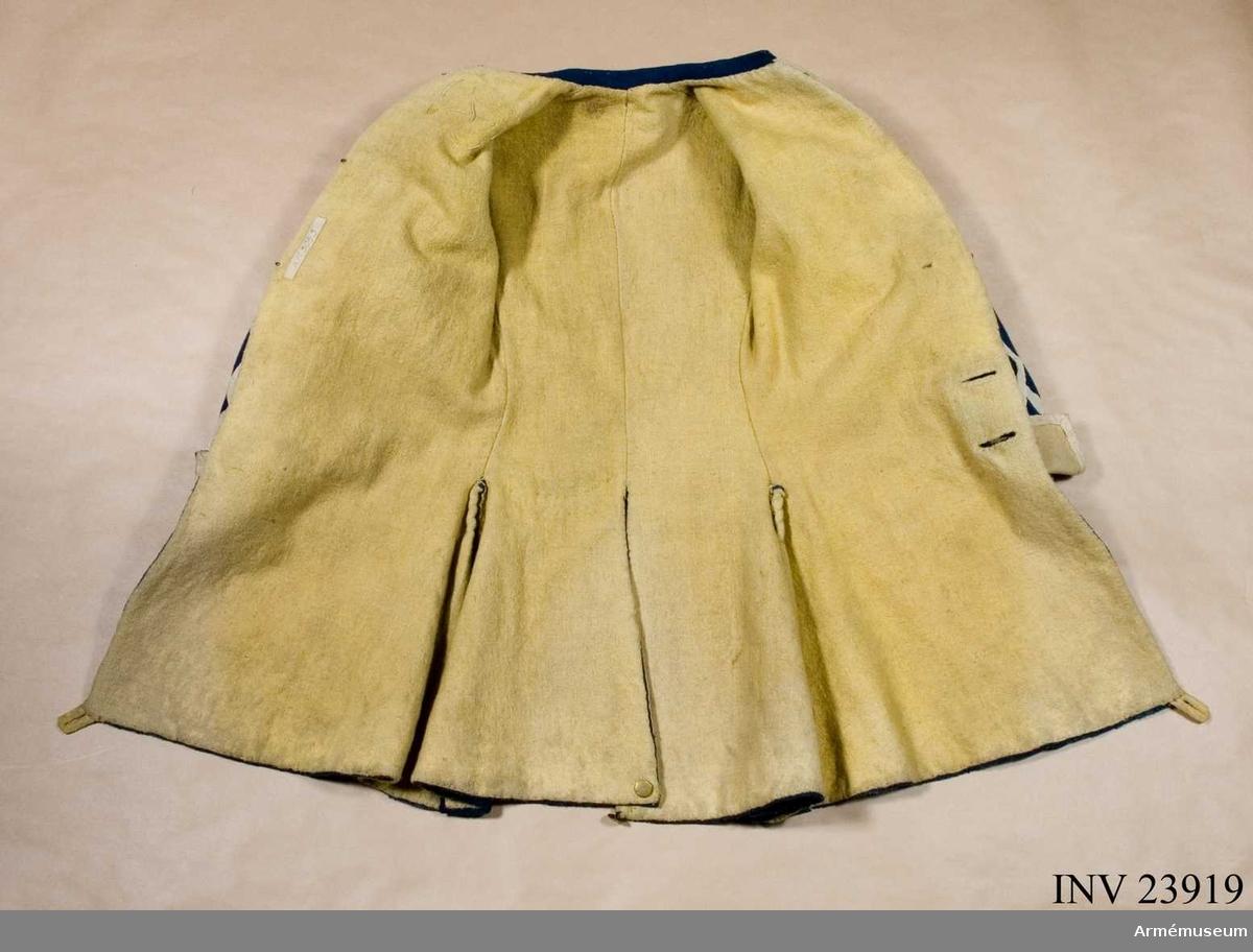 Grupp C I. Ur uniform för spel vid Södermanlands regemente i huvudsak gällande för indelta infanteri 1765-1779. Består av: rock, väst, byxa, mössa, kläde m vapenplåt, sko, gehäng. Rock med prydnader för spelet; mellanblå med gul rabatt, svalbon och ärmuppslag. Vit redgarnsdekor bruklig för spel. Rocken har sammanlagt 23 knappar. Knapparna i framkanten fastträdda med vitt band från avigsidan. En knapp i vardera skört (en ny). Två knappar på ficklocken (höger sida fattas en). Rocken är fodrad med gult ylletyg. Rocken ihopfästes med hyskar och hakar.