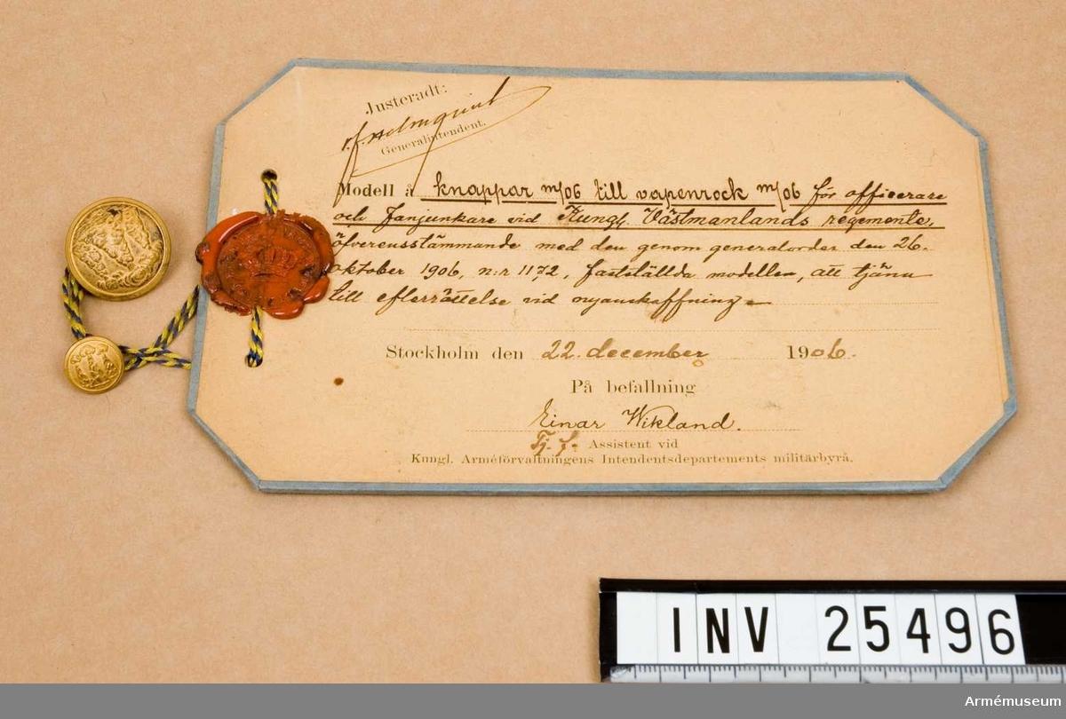 Samhörande gåva: 25496-7, knappar.Knapp m/1906.Grupp C I.Större knapp m/1906 till vapenrock m/1906 för Västmanlands reg. Modellexemplar.