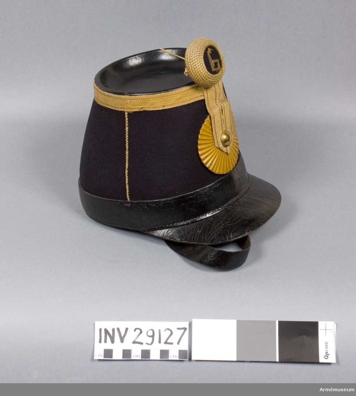 Grupp C I. Käppi m/1854 fastställd enligt g.o. 30/12 1854 (infanteriet allmänt). Ur uniform m/1858-60, livplagg m/1860, för manskap vid Västgöta regemente Består av: 1. Vapenrock m/1860 2. Axelklaffar med Västgöta regementes nr 6 3. Byxor m/1860 4. Käppi m/1854 5. Pompong med Västgöta regementes nr 6 6. Snörkängor m/1863 7. Spännhalsduk m/1857, förkommen. 8. Patronkök m/1864, med 9. Livrem med spänne  Käppin är av blått ylle med svart läderkant längst ned och svart läder på toppen. Dekor av gula band och på sidorna tunna snoddar. Mitt fram en gulmålad läderrosett med metallknapp i mitten. Hakband av läder med spänne. Insidan av läder är något nött. Inget band i öljetterna.