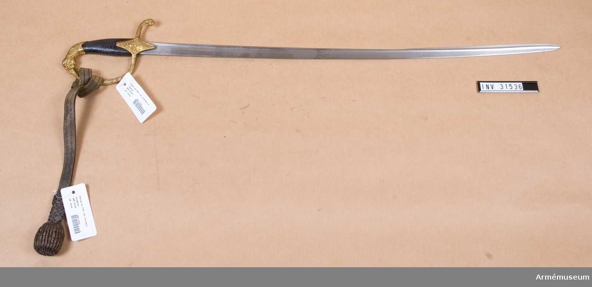 """Grupp D II.  Klingan är krökt och damaskerad samt har förstärkt rygg och längt ned tveeggad klack.  Fältet är av förgylld mässing. Kaveln har närmstt ovalt tvärsintt och är klädd med svärtat fiskskinn.  Nedåt är den rätt bred, men uppåt av smalnar den.Upptill finnes en ganska lång framåtböjd kappa. som längst fram är ciselerad i form av ett lejonhuvud.  Baktill begrähas detta huvud av par ingraverade ränder och ab ett slätt, på mitten litet insänkt ring-liknande fält.  Resten av den bågböjda kappan har nära nog cirkelrunt tvärsnitt och är prytt med ciselerade,stilliserade blomornament på finprickig grund.  Nedtill på vardera sidan är kappans underkant insvängd.  Parérstången har frysidigt tvärsitt, är baktill nedböjd och avslutas av en påisidorna medmettaciceler blomornament prydd knapp.  På över-och undersidan är paréstångens bakre del slät, men på sidorna är den prydd med cielserade, rnkla ornament på finprickig grund inom föerböjd kantram. Framtill övergår parérstången i båge i handbyygeln, vilken har fyrkantigt tvärsintt, dock med inner -och yttersidan svagt välvd.  De bägge sistnämnda sidorna äro prydda med en cielerad, stilliserad blomranka på finprickig grund inom förhöjd kantram.  Handbygeln ör ganska smal och dess övre ände är instuken i lejonhuvudets mun.  Vid korset finnes ett par kraftiga styrskenor, vilka nära nog ha formen av en romboid.  Nedtill skjuta de ned ganska långt över baljan och upptill gå de ganska högt upp på kaveln.  Vardera styskenan är prydd med cieleratt Minervahuvud på finprickig grund inom fint tvärrefflad kantram.  Baktill på parérstångens undersida finnes en oval stämpel med nament C.A.F.Ek.  Sabeln liknar mycket dragonofficerssablarna """"m/1845"""" (Se A.M. 1932:7553 och 7555) ochj avviker från desa egentligen endast i fråga om klingans form och fråga om detaljer i orneringen.   Samhörande nr AM.031536-AM.031538 sabel, balja, portepé."""
