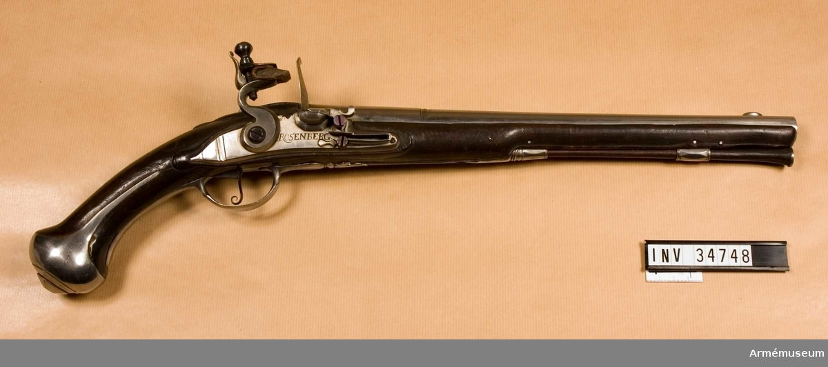 Grupp E III a. Pistol med flintlås, 1720-30 talet. Möjligen tillverkad för något svenskt i Pommern stående kavalleriregemente. Projekt?  Kammarstycket märkt på V sidan med numret 50.  På svansskruvsstjärten No 1. På låsblecket Rosenberg (Stralsund). Beslag av polerat järn. På kolvens V sida ovanför kolvkappan numret 50.  Pistolen är exakt lik pistol nr 1932:11927 vilkens modellkammar- nummer tyder på att pistolerna en gång gått i par.