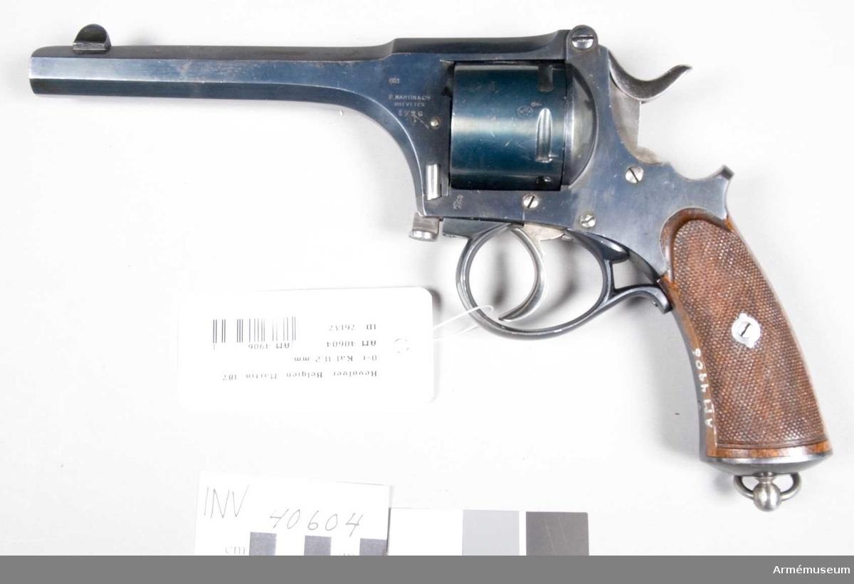 """Grupp E III.  Revolvern är helt blånerad med undantag av hane och avtryckare, vilka är blankpolerade. Pipan är 14,7 cm lång. Den är sjukantig och så utformad, att den utgör även främre och övre delen av ramen. Trumman har plats för sju patroner, och på densamma förekommer Lieges stämpel samt ett krönt N.Den senare förekommer även på flera av vapnets delar. På ramens vänstra sida står """"F. Martin & Cie Brevetés"""" samt tillverkningsnr 1726. På samma sida nedanför trumman finns en otydlig stämpel, som syns vara en krönt grip. På motsvarande sida står """"Agier Fondu"""". Kolvskenorna är av refflad brun valnöt."""