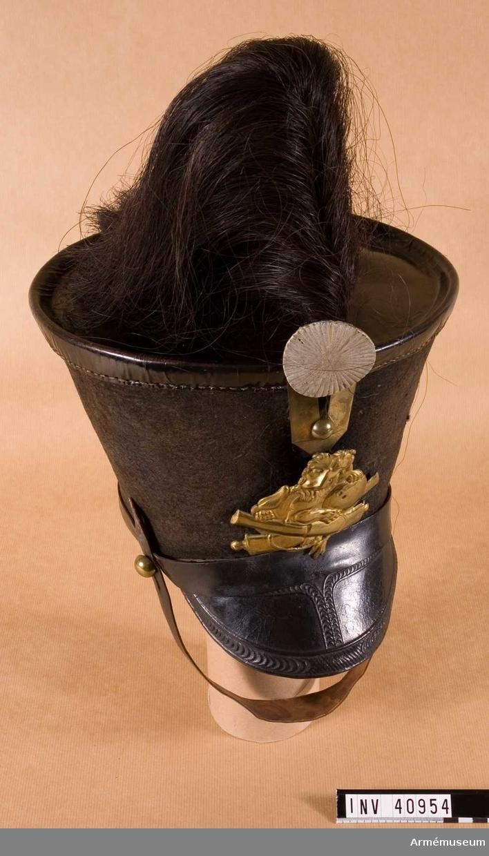 Grupp C I. Ur uniform för manskap vid Åkande artilleriet 1815-27. Består av jacka, byxor, tschakå med plym, stövlar, sporrar, skärp, ägiljett, halsduk, kartusch med rem, sabelkoppel, sabelhandrem, luntstake med lunta, vapenplåt.
