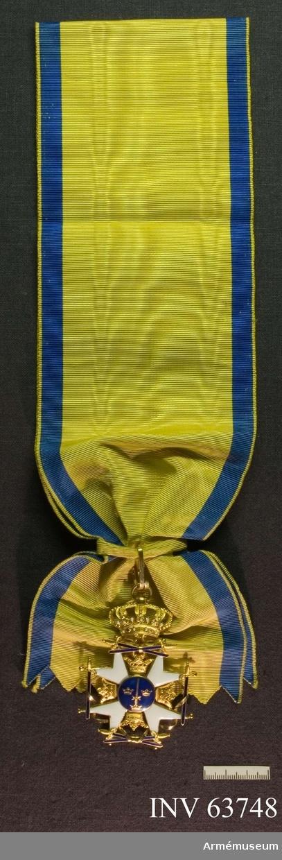 Grupp M II.     Ett vitt, i guld infattat Andreaskors (emaljen mycket skadad å korsets sidor) med 8 uddar, slutande i gyllene kulor och gyllene kronor mellan armarna.    Åtsidan: Mitt i korset en blå glob med ett upprättstående gyllene svärd mellan Sveriges tre kronor. Över och under korsets två korslagda blåemaljerade svärd, på högra och vänstra sidan två, likaledes blåemaljerade, med fästena uppåt, stående svärd, samtliga svärden omvirade av guldbälten, som slutar på ordenstecknets frånsida.  Frånsidan: Guldbältena från åtsidan slingra sig om korsets armar. Globen innehåller ett upprättstående gyllene svärd, omgivet av en gyllene lagerkrans samt däröver i guldbokstäver: PRO PATRIA. Över korset en stor kunglig krona.   Ordenstecknet sitter på ett brett band.