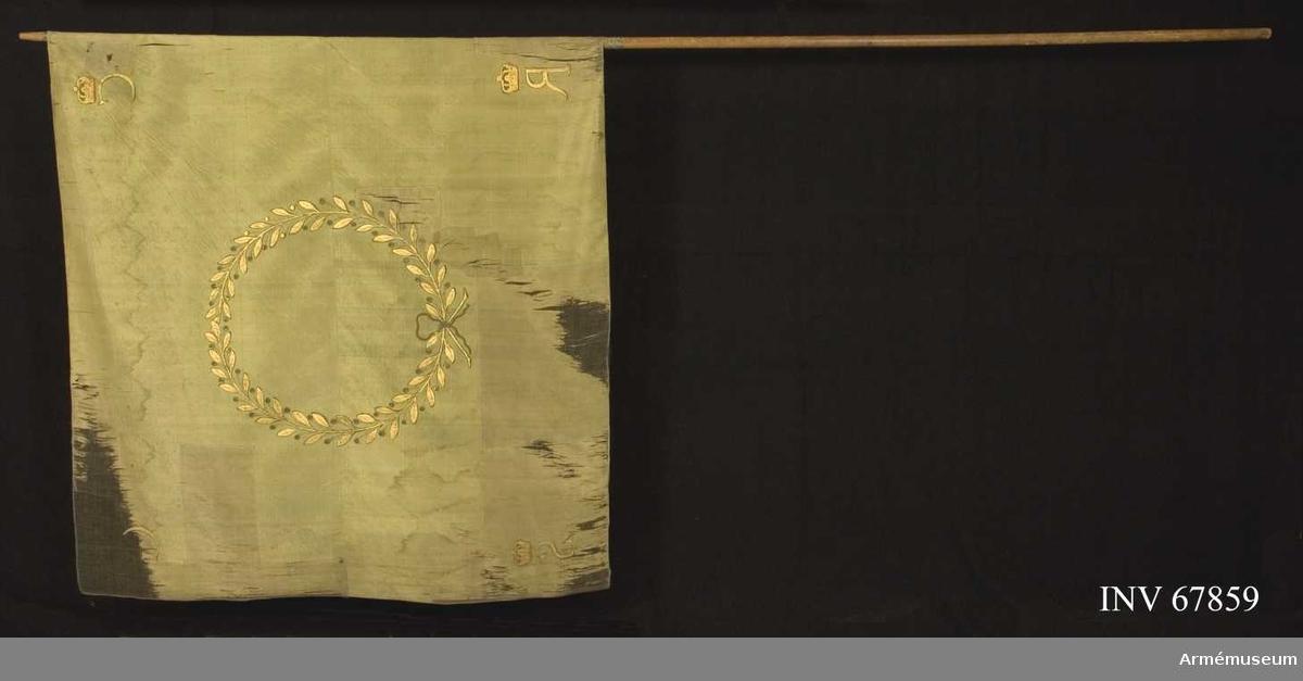 Duk: Tillverkad av enkel grön sidentaft, sydd av två horisontella våder.  Dekor:  Målat omvänt lika på båda sidor, en liten krans av två guldlagerkvistar med omväxlande blad och bär, nedtill ihopbunden med en rosett, allt i guld. I hörnen guldbokstäver: C G R S, krönta med slutna guldkronor med rött innerfoder.  Fäst vid stången med förgyllda spikar på ett grönt sidenband (linne?), b: 14 mm. Bandet lindat runt stången 70 mm ner på stången. Stång av omålad furu.