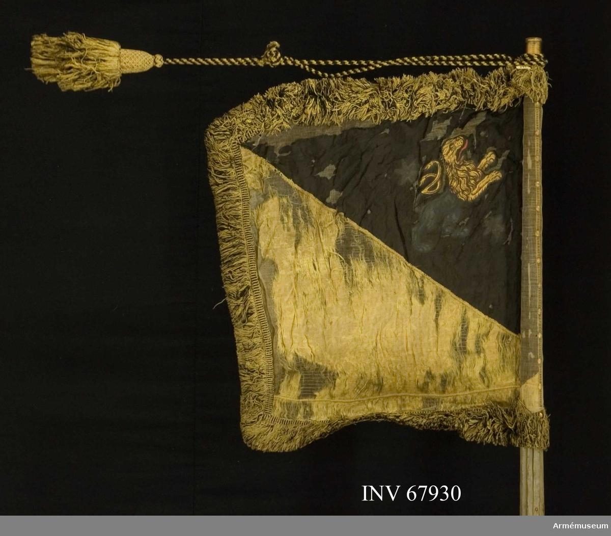 Duk: Enkel, tillverkad av damast, gul och svart, ganska trasig, skarvad nedtill horisontellt.   Dekor: Diagonalt delad i två fält, det övre, inre svart, det nedre, yttre gult; i inre hörnet målat omvänt lika på båda sidor ett upprätt lejon, övre halvan i brunskuggat guld,nedre i mörkgrått, följt av två stjärnor i svartskuggat silver (Västergötlands vapen).   Frans: Dubbel, i svart och gult silke, fäst vid stången med tre rader tennlickor på svarta och gula band.   Stång: Tillverkad av trä, kannelerad; holk av mässing; doppsko av läder, fastsydd.