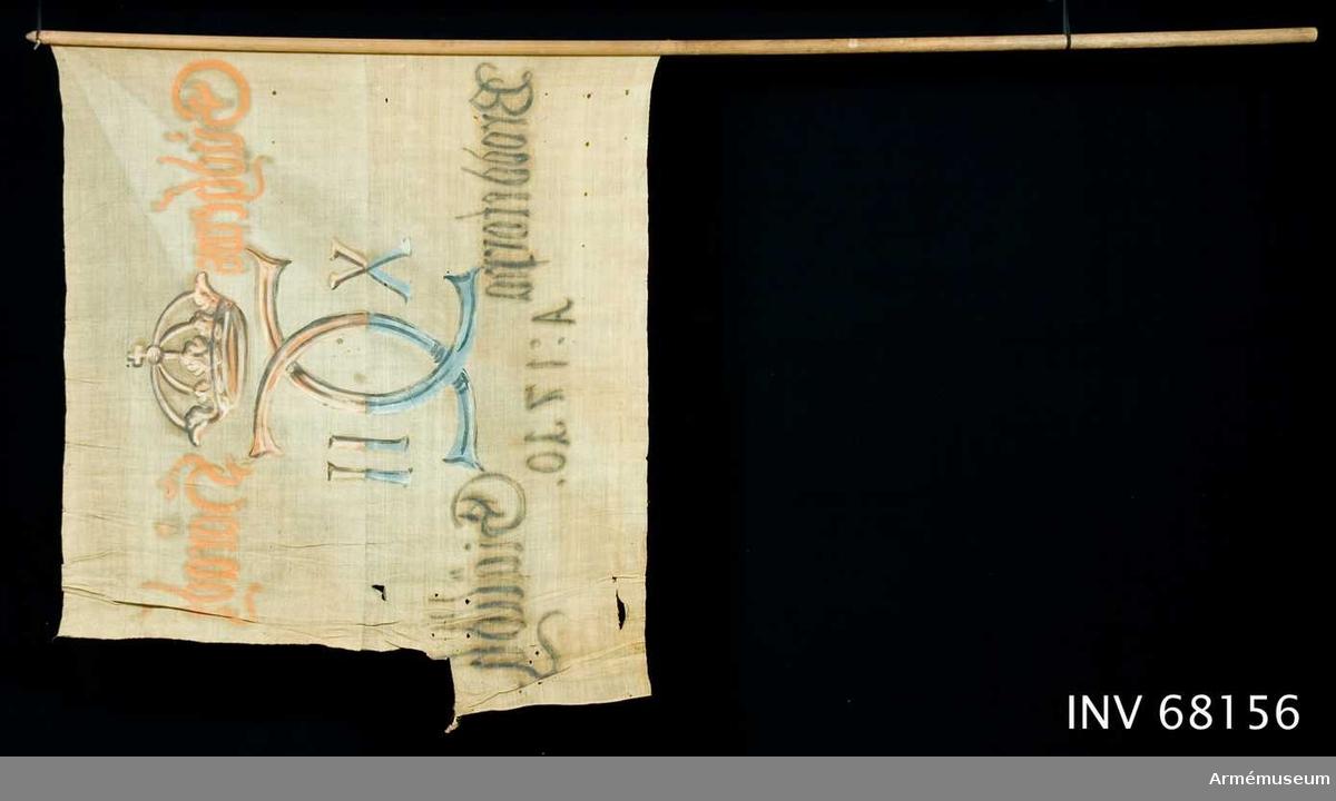 Duk: Tillverkad av enkel vit linnelärft, sydd av två horisontella våder. Fäst med en rad järnspik på ett rött och vitt linneband.  Dekor: Målad endast på dukens insida i mitten, Carl XII:s namnchiffer, dubbelt C med X-II på ömse sidor, krönt med sluten krona. På den övre våden i gult och brunt, på den nedre i blått och svart. Text på ömse sidor om chiffret, upptill i gult och nedtill i svart. Under chiffret text i svart.  Stång: Tillverkad av trä. Profilerad knopp upptill.