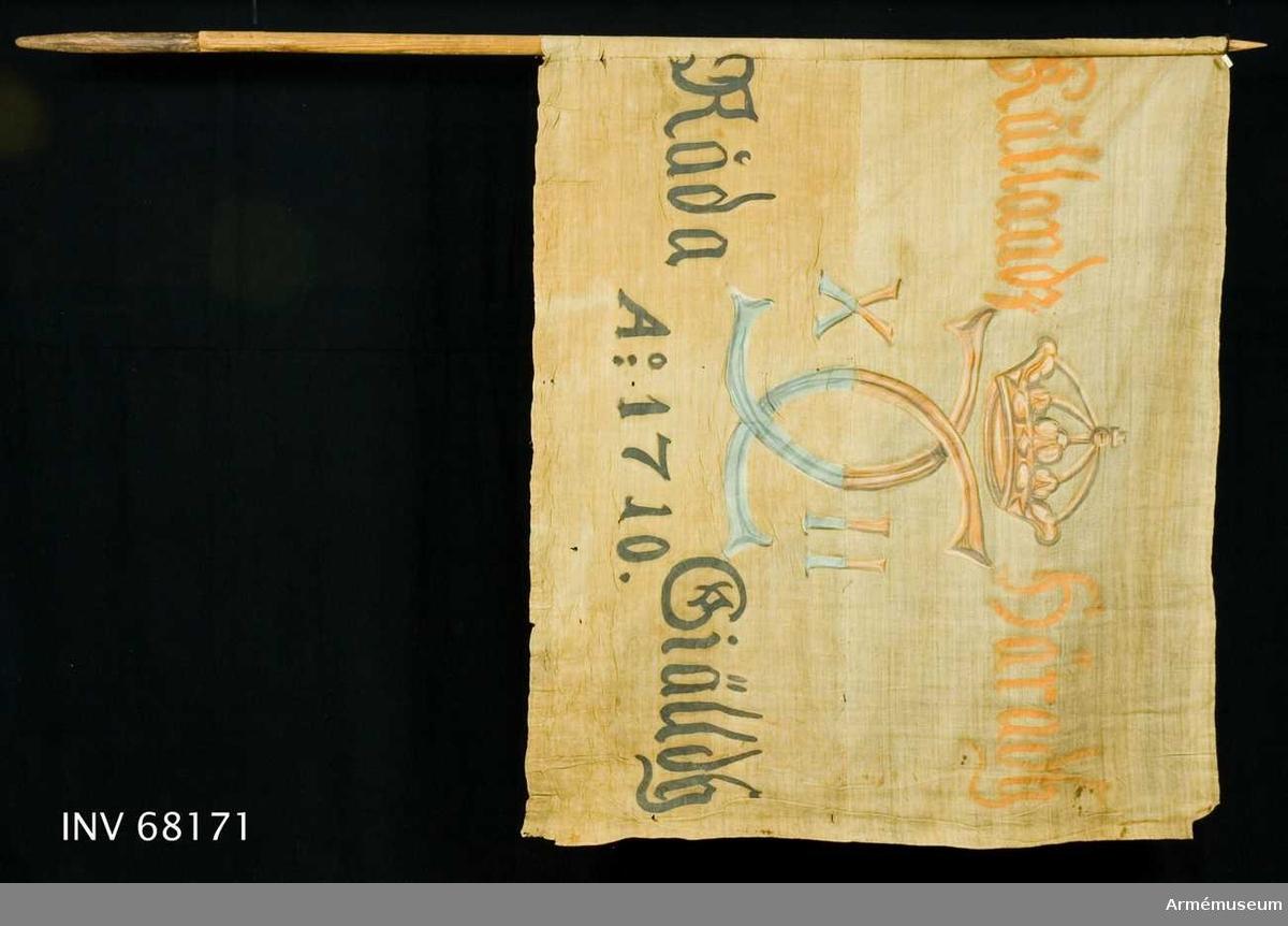 """Duk: Tillverkad av enkel vit linnelärft. Sammankastad av två horisontella våder. Stad i över- och nederkanten, det vill säga horisontella ytterkanterna. Duken fastsydd runt stången.  Dekor: Målat endast på dukens insida (kronan och namnchiffret dock ifyllt på nedre sidan). I mitten Carl XII:s namnchiffer, dubbelt C, krönt med sluten krona.   Text på ömse sidor om chiffret, upptill i gul och nedtill i svart. Under chiffret text i svart.  Stång: Tillverkad av trä. Spetsig upptill. Nedtill """"laxat"""" i en extra träförlängning."""