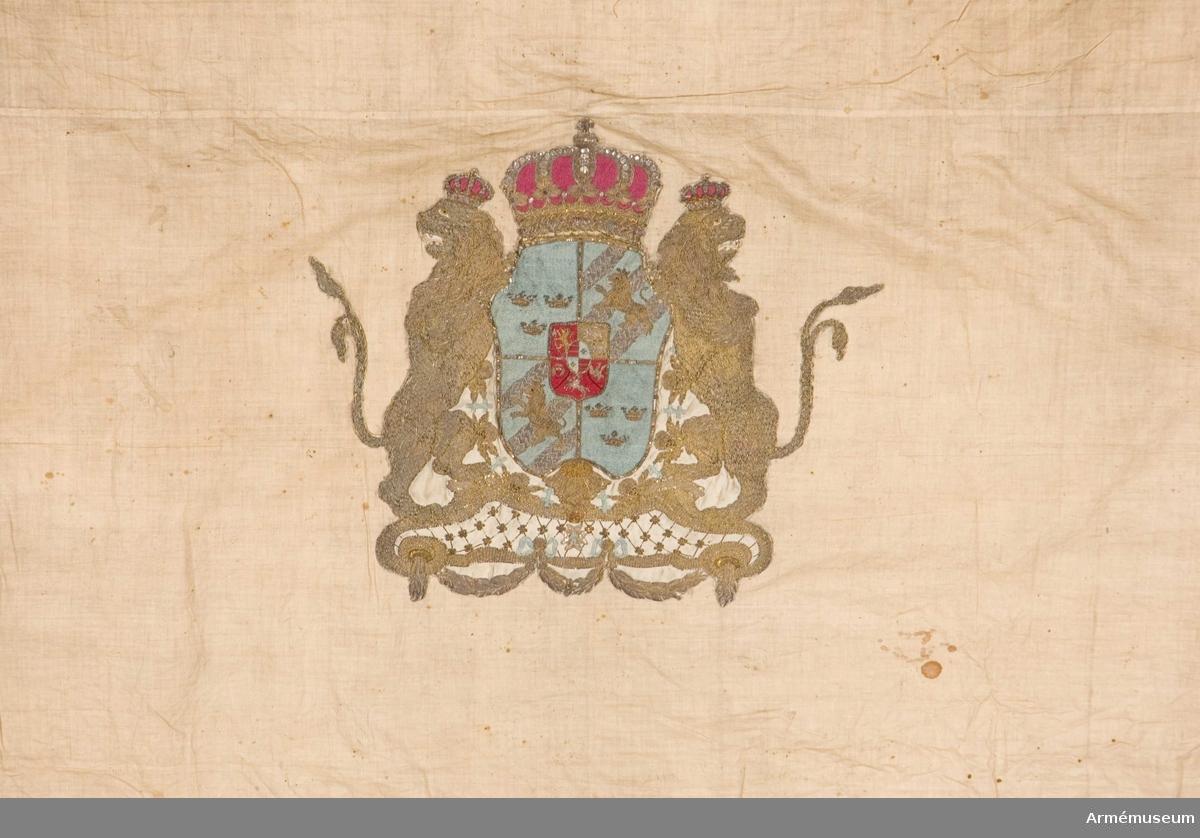 Fanduk av vit lärft med på mitten applicerat det svenska riksvapnet, huset Holstein-Gottorp, utfört i broderi.
